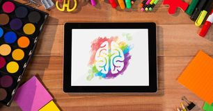 Tablet on a school table with colored brain on screen. Digital composite of Tablet on a school table with colored brain on screen Royalty Free Stock Photography