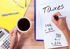 Taxes text written on page with coffee and calculator. Digital composite of Taxes text written on page with coffee and calculator Royalty Free Stock Image