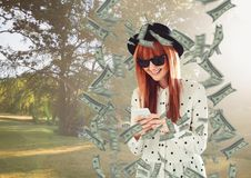 texting money. hipster with hat and phone in the park, money around. stock photo