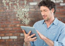 Texting money. man with tablet. Money coming up from tablet. Royalty Free Stock Photos