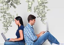 Texting money. young couple with laptops. Money coming up from laptops. Stock Photos