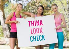 Think Look Check text and pink breast cancer awareness women holding card. Digital composite of Think Look Check text and pink breast cancer awareness women Royalty Free Stock Photos