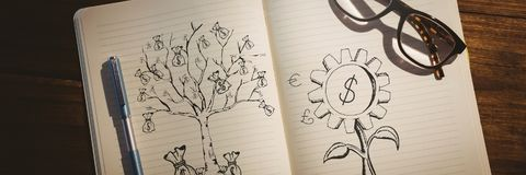 Tree and fower drawings with money in notepad Stock Image