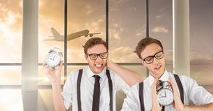 Twin hipster men holding clocks in airport stock photography