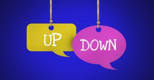Up Down text on hanging paper speech bubbles. Digital composite of Up Down text on hanging paper speech bubbles Stock Photo
