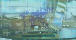 Digital composite video of stock market data processing against man using laptop in background