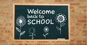 Welcome back to school text and flowers on blackboard