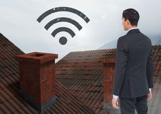 Wi-fi icon and Businessman standing on Roofs with chimney and fog. Digital composite of Wi-fi icon and Businessman standing on Roofs with chimney and fog Royalty Free Stock Photos