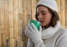 Woman against wood with warm gloves hat and scarf and cup Royalty Free Stock Images