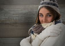 Woman against wood with warm hat and scarf and gloves Royalty Free Stock Image