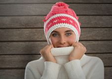Woman against wood with warm woollen hat and jumper. Digital composite of Woman against wood with warm woollen hat and jumper Royalty Free Stock Photo