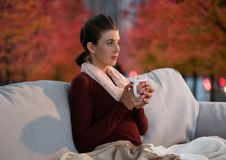 Woman in Autumn with cup in surreal red trees and lights Royalty Free Stock Photography