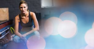 Woman crouching in gym and blue pink bokeh transition Royalty Free Stock Image