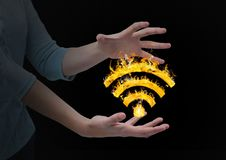 Woman hands with WIFI fire icon between. Black background. Digital composite of woman hands with WIFI fire icon between. Black background Royalty Free Stock Image