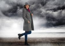 Woman in hat and warm clothes under dark clouds and sea Royalty Free Stock Photo