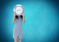 Woman holding clock in front of blue background Stock Photos