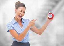 Woman holding clock in front of bright blurred background Royalty Free Stock Photo