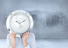 Woman holding clock in front of city imprinted on wall in room Royalty Free Stock Photo