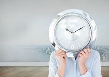 Woman holding clock in front of city in room Royalty Free Stock Photo