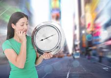 Woman holding clock in front of city rush Stock Photography