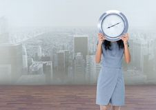 Woman holding clock in front of city Royalty Free Stock Photos