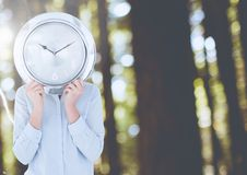 Woman holding clock in front of forest. Digital composite of Woman holding clock in front of forest stock images