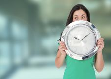 Woman holding clock in front of green blur Stock Image