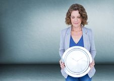 Woman holding clock in front of room Stock Image