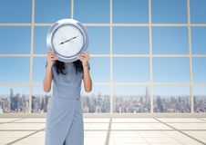 Woman holding clock in front of windows with city skyline Stock Photo