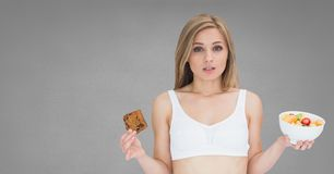 Woman holding deciding healthy and unhealthy food choice. Digital composite of Woman holding deciding healthy and unhealthy food choice Royalty Free Stock Photo