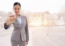 Woman Holding keys in front of houses stock photo