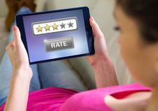 Woman holding tablet with star ratings review button. Digital composite of Woman holding tablet with star ratings review button royalty free stock photography