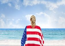 Woman holding a USA flag in the beach. Digital composite of Woman holding a USA flag in the beach Royalty Free Stock Photography