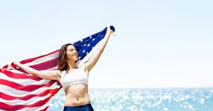Woman holding a USA flag in the beach. Digital composite of Woman holding a USA flag in the beach Stock Photography
