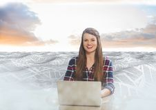 Woman on laptop in sea of documents under sky clouds. Digital composite of Woman on laptop in sea of documents under sky clouds Royalty Free Stock Images