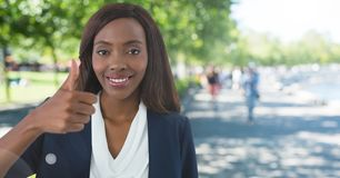 woman in park smiling with thumbs up stock images