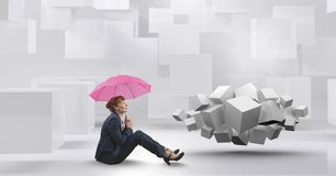Woman sitting with umbrella next to geometric surreal cubes. Digital composite of Woman sitting with umbrella next to geometric surreal cubes royalty free stock images