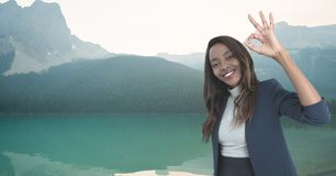 Woman smiling with ok sign in the mountains. Digital composite of woman smiling with ok sign in the mountains royalty free stock photos