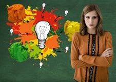 Woman standing ext to light bulb with colorful crumpled paper balls in front of blackboard Royalty Free Stock Photos