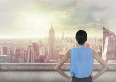 Woman standing hands on hips looking across skyline. Digital composite of Woman standing hands on hips looking across skyline Royalty Free Stock Photography