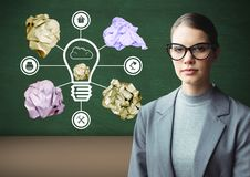 Woman standing next to light bulb with crumpled paper balls in front of blackboard. Digital composite of Woman standing next to light bulb with crumpled paper Stock Image