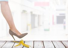 Woman stepping on banana peel about to slip mistake Royalty Free Stock Image