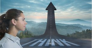 Women facing arrow pointing up on road. Digital composite of Women facing arrow pointing up on road Royalty Free Stock Photography