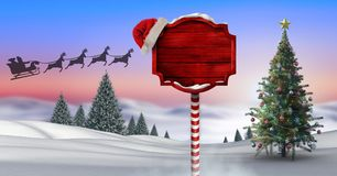 Wooden signpost in Christmas Winter landscape with Christmas tree and Santa`s sleigh and reindeer`s. Digital composite of Wooden signpost in Christmas Winter Stock Photo