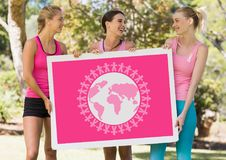 World planet graphic and pink breast cancer awareness women holding card Royalty Free Stock Images