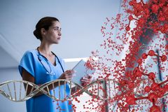 Worried doctor woman sitting with 3D DNA strand and cells Royalty Free Stock Photography