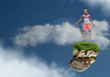 Young boy on floating rock platform in sky jumping stock images
