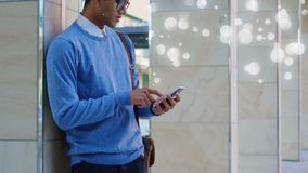 Young man using his mobile phone surrounded by white bubbles effect. Digital composite of a young mixed-race man using his mobile phone standing against a wall stock footage