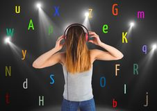 Young woman listening music with colour letters around. Black back Stock Photos