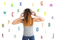 Young woman listening music with colour letters around. White back. Royalty Free Stock Image